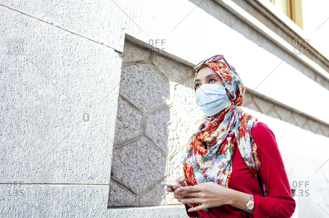 Woman in hijab wearing protective face mask holding smart phone while walking by wall during COVID-19