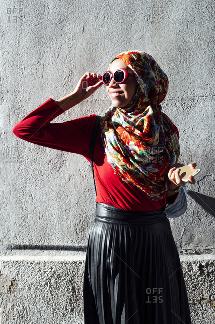 Mid adult Muslim woman holding sunglasses while looking away against concrete wall on sunny day