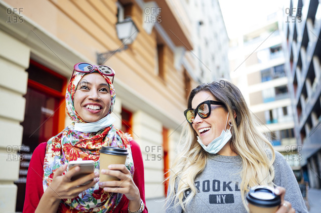 Happy female friends laughing while holding disposable cups in city during COVID-19
