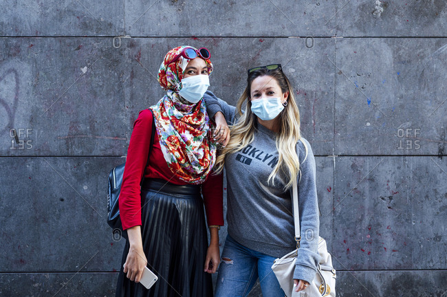 Woman wearing face mask while standing with hand on Muslim friend's shoulder against gray wall during pandemic