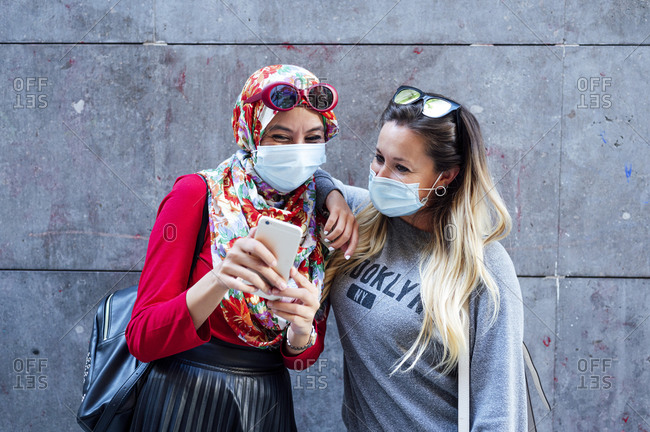 Muslim woman sharing smart phone with female friend against gray wall