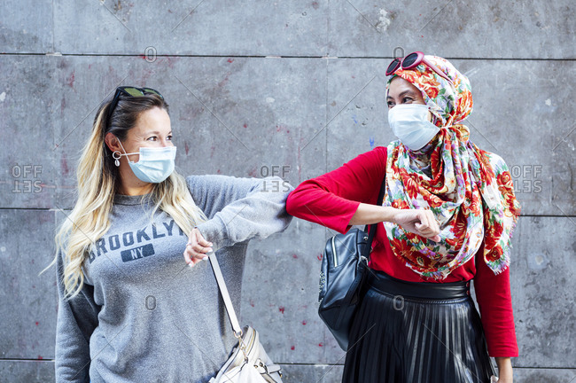 Female friends wearing protective face masks greeting with elbow bumps during COVID-19