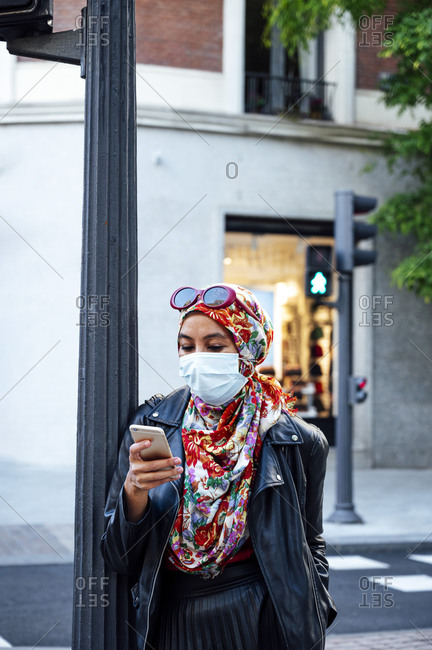 Mid adult woman in floral hijab using smart phone leaning on pole in city during COVID-19