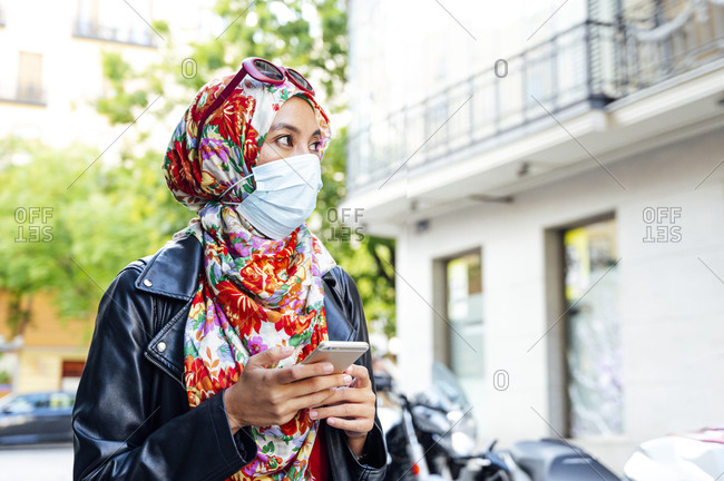 Woman in floral hijab holding mobile phone looking away in city during coronavirus