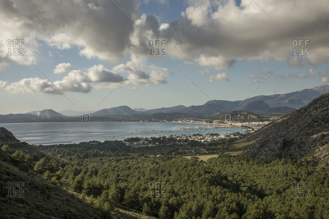 Spain- Mallorca- Port de Pollenca- Forested valley with coastal town and Bay of Pollenca in background