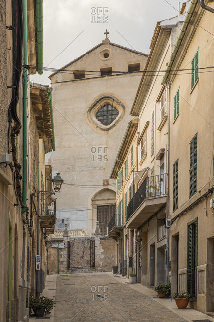Spain- Mallorca- Pollenca- Empty alley between old town houses with church in background