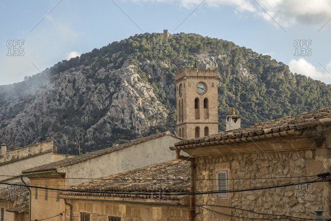 Spain- Mallorca- Pollenca- Bell tower rising over old town houses with mountain in background