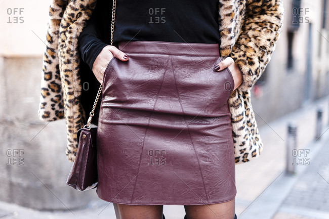 Woman wearing fur coat and mini skirt standing with hands in pockets
