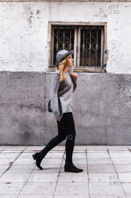 Young woman with hat walking by building on street