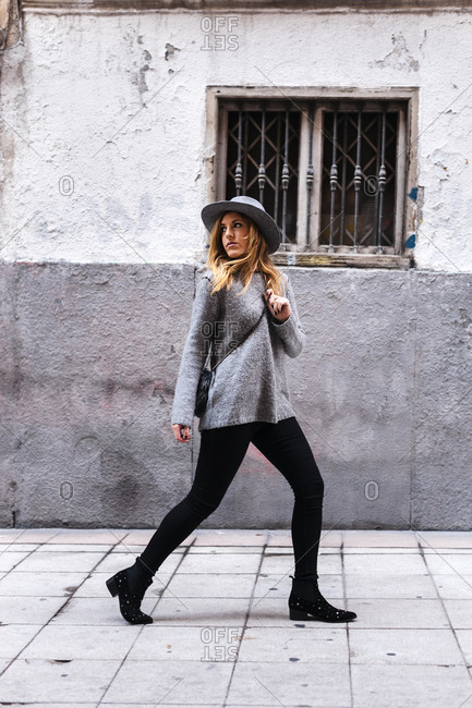Attractive fashionable woman with hat looking away while walking on street