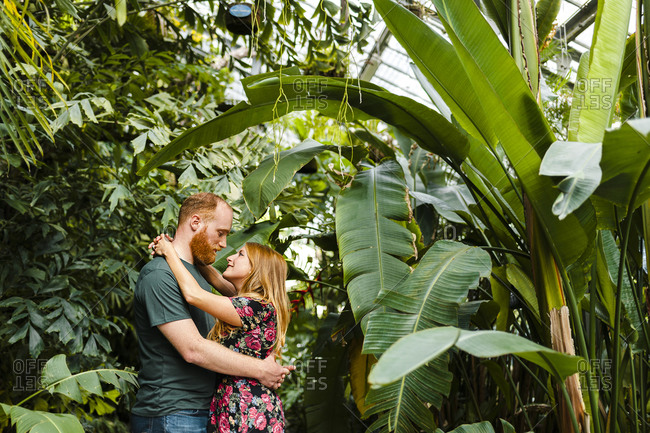 Redhead heterosexual couple embracing each other while standing in park