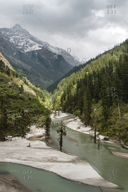 Drone view of Parvati River flowing along forested valley in Himalayas- India