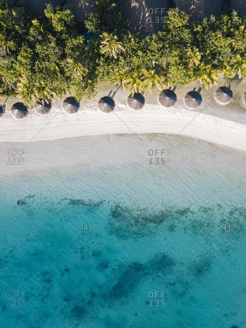 Maldives- Kaafu Atoll- Hudhuranfushi- Aerial view of row of huts along sandy coastal beach of Hudhuranfushi island
