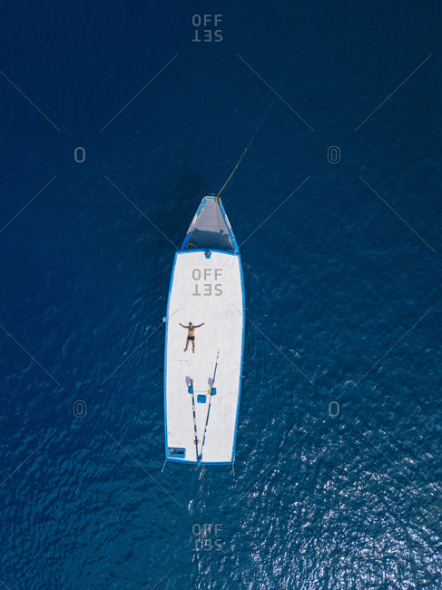 Aerial view of shirtless man relaxing on roof of boat drifting in blue waters of Arabian Sea in summer