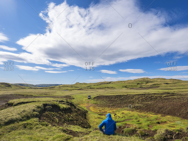 Clouds over male hiker sitting on grass and admiring remote Icelandic landscape