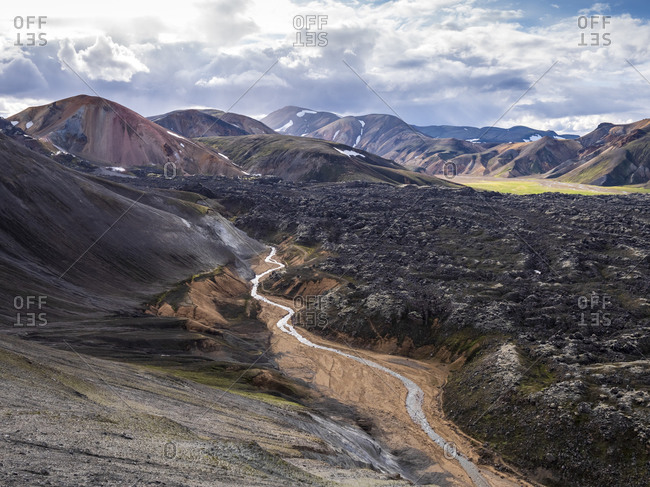 Scenic view of stream flowing across volcanic valley in Landmannalaugar