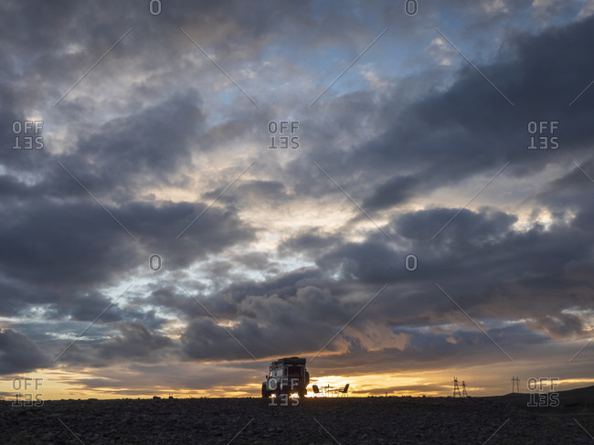 Gray clouds over off-road car parked in remote Icelandic location at dusk