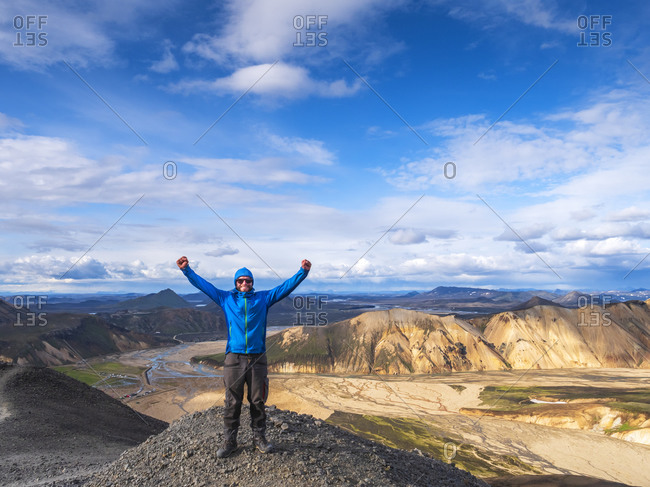 Hiker posing with raised arms on top of volcanic hill in Landmannalaugar