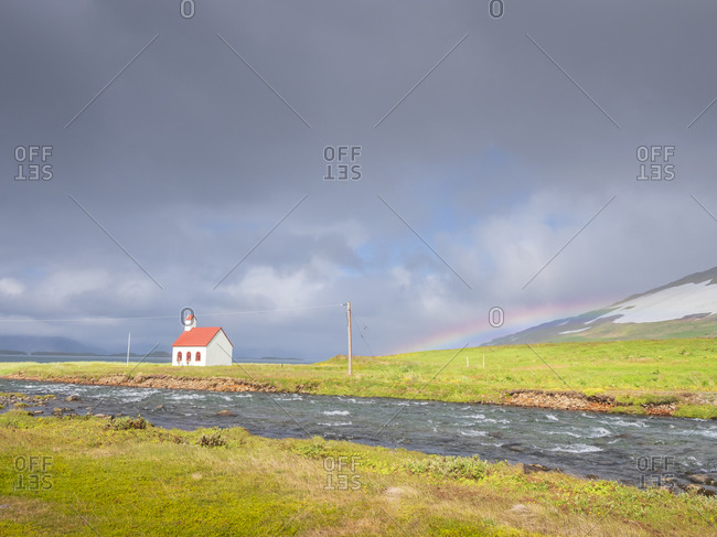 Gray clouds over river flowing in front of remote Unadsdalskirkja church- Iceland