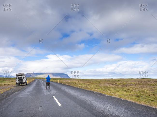 Man standing in middle of remote asphalt road- Iceland