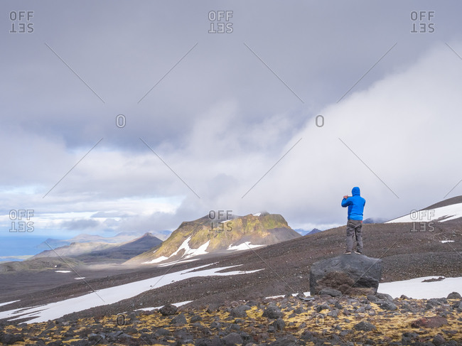 Male hiker standing on top of boulder in Snaefellsjokull National Park- Iceland