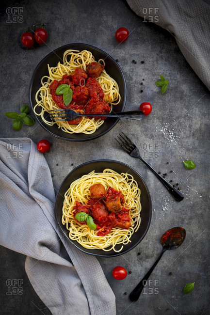 Two bowls of spaghetti with vegetarian polpette and basil