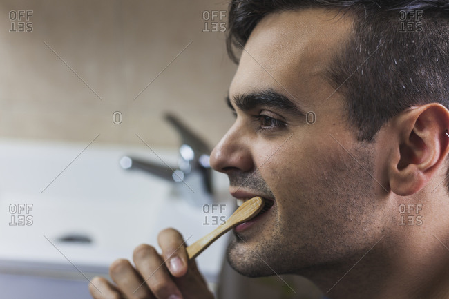 Young man brushing teeth with bamboo toothbrush