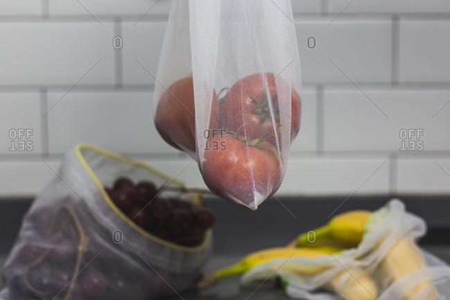Reusable bag with tomatoes- bananas and grapes