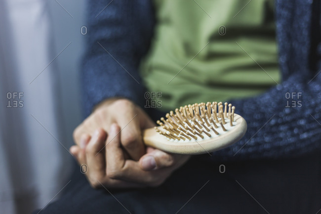 Young man holding bamboo hair brush