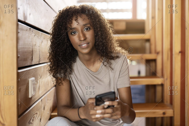 Young woman using mobile phone while sitting on staircase at home