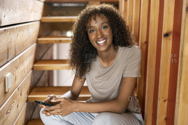 Woman using mobile phone while smiling on staircase at home
