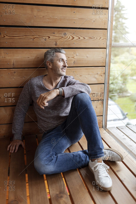 Smiling man looking through window while sitting on floor at home