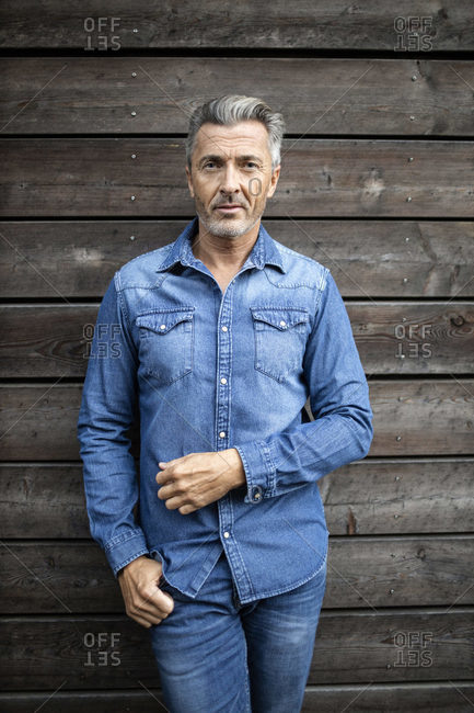 Mature man leaning on wooden wall