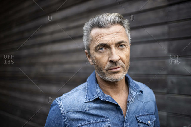 Mature man staring while standing against wooden wall