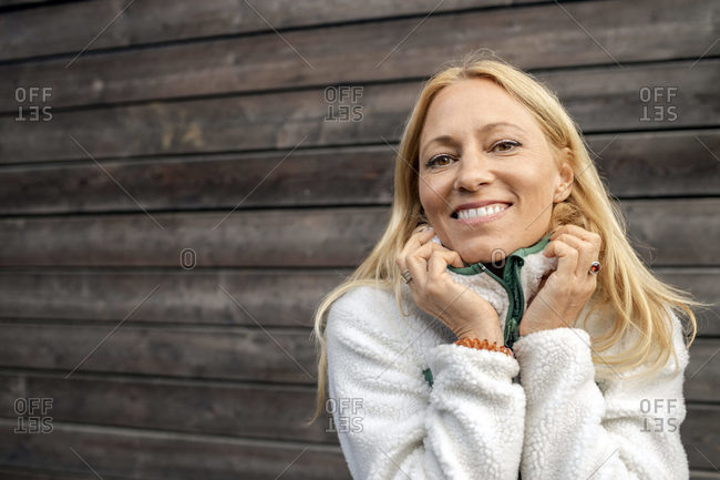 Woman wearing warm clothing smiling while standing against wooden wall