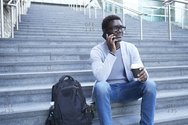 Businessman answering phone call while holding disposable coffee cup on staircase