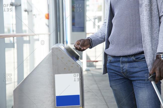 Businessman scanning ticket at gate of railroad station