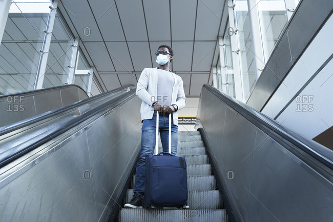 Businessman wearing protective face mask holding luggage while standing on escalator at station