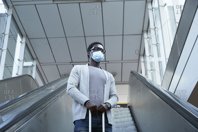 Male entrepreneur wearing protective face mask holding luggage while standing on escalator at station