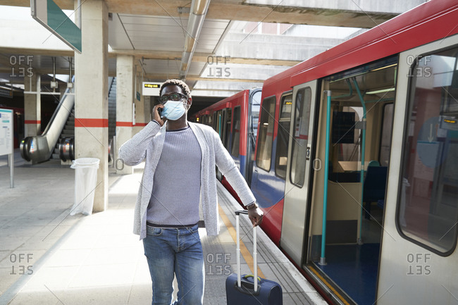 Mature businessman wearing protective face mask talking on phone at railroad station platform