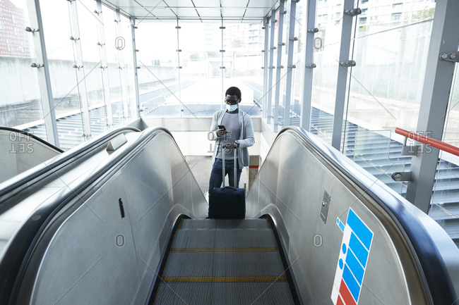 Businessman with luggage using smart phone while standing on escalator at railroad station during COVID-19