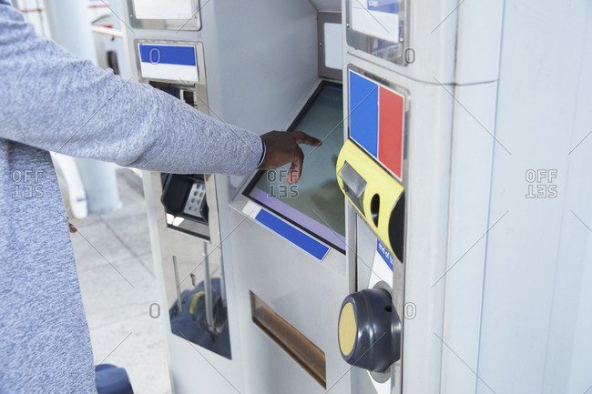 Hand of male commuter using ticket machine at railroad station