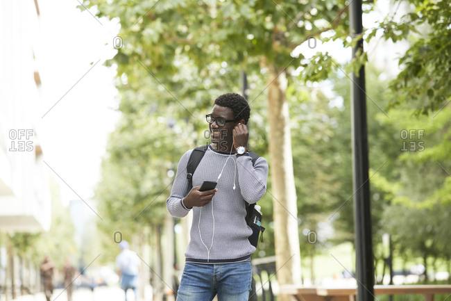 Smiling businessman adjusting in-ear headphones while looking away