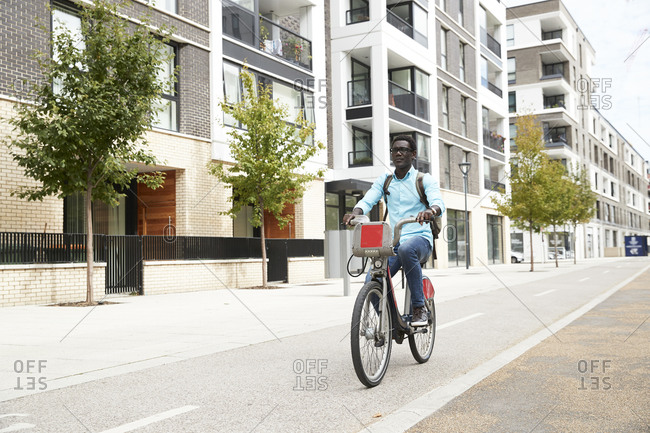 Mature male commuter riding bicycle on street in city