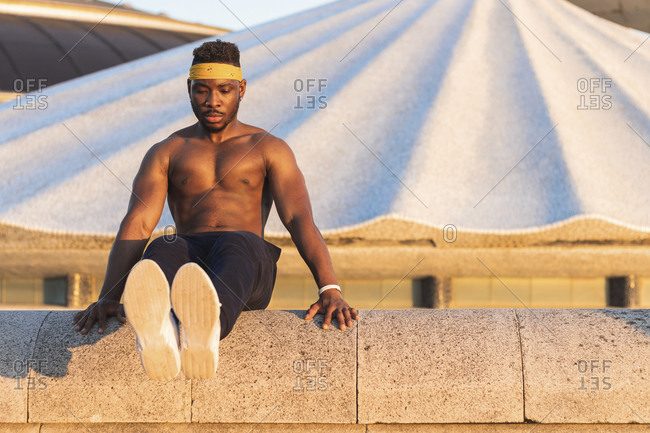 Athlete doing abdominal muscle exercise while sitting on retaining wall at park