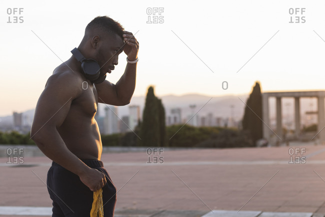 Shirtless young man standing with hand in hair at park