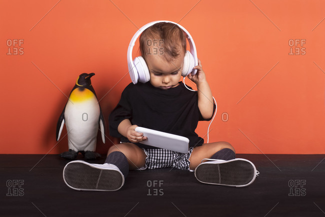 Baby girl wearing headphones using mobile phone while sitting by toy penguin against orange background