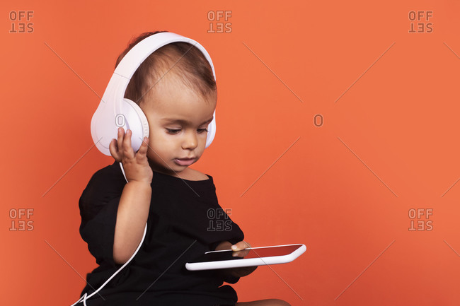 Cute baby girl wearing headphones using mobile phone while sitting against orange background