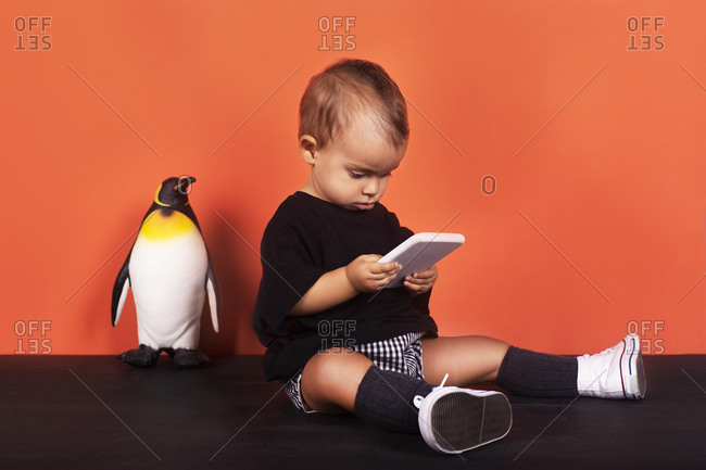 Baby girl playing in mobile phone while sitting by toy against orange background