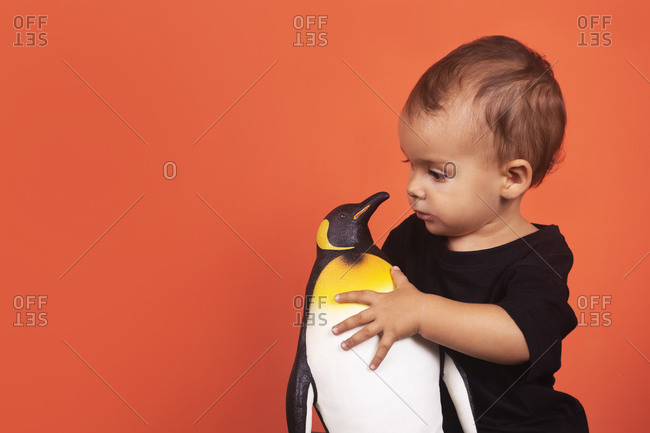 Baby girl playing with penguin toy while sitting against orange background